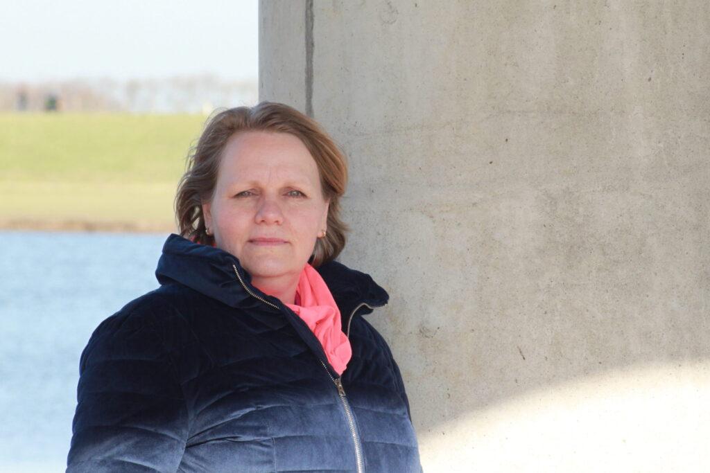 Maak kennis met provocatief coachen Desiree Braams leunend tegen een pilaar eigenaar van Coaching bij Dees